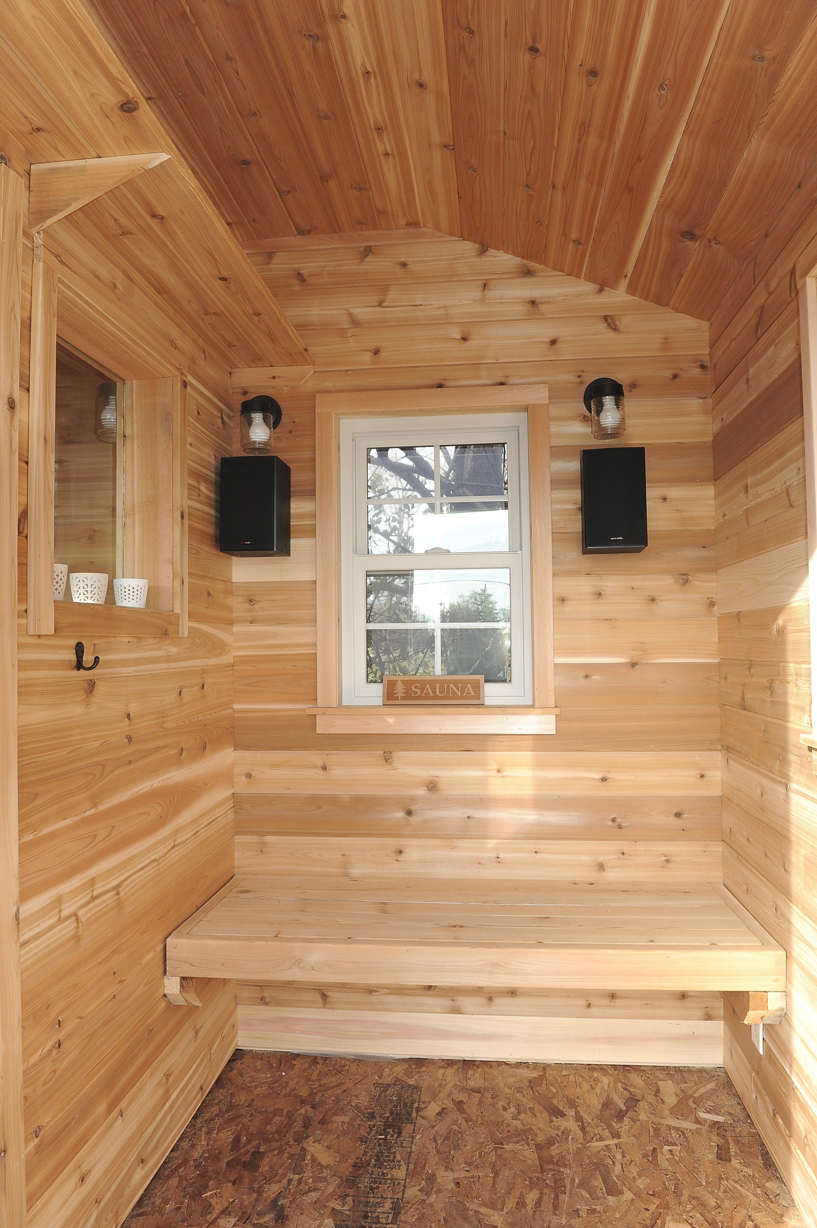 A changing room with windows and hooks and space to chill out.