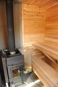 Wood burning sauna:  feed from the outside or inside?