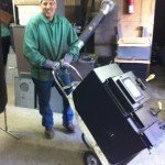 Employee Dave wheeling out another authentic sauna stove for a satisfied customer who isn't afraid to live.