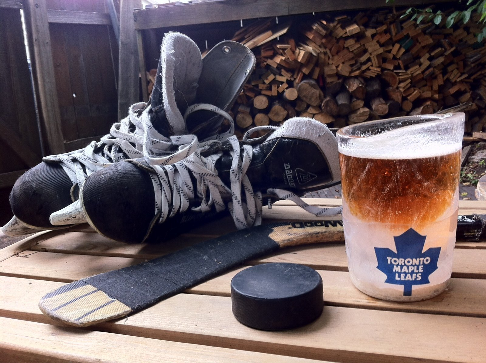 nICE mug and NHL with hockey stick and skates and puck.  A drinking glass made out of ice.