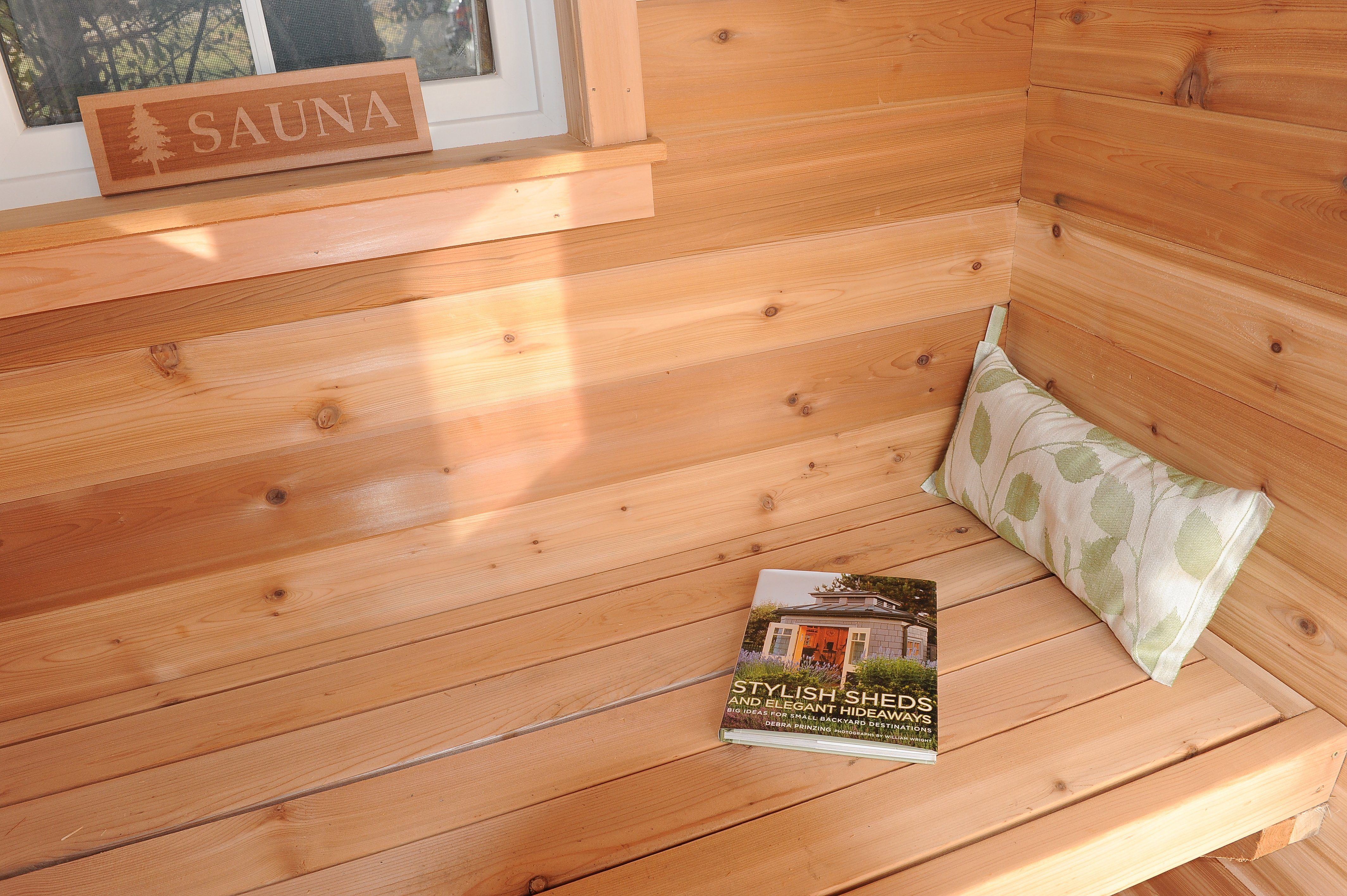 "A cozy sauna changing room bench can double as a great hang out space - an ""up North"" lake cottage feeling steps out your back door."